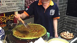 Jianbing - A vendor spreads flour mixture into a pan to make jianbing