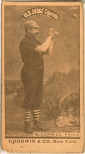 A baseball player is shown on his right profile, standing in his uniform.