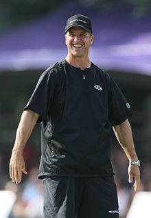 Color photograph of tall, smiling man (John Harbaugh) dressed in black sport shirt, black practice shorts, and black baseball cap.