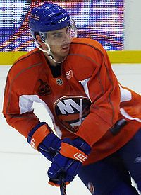 Hockey player in orange uniform. He skates across the ice, holding his stick, and looks over his left shoulder.