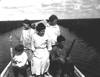 """John Kunkel Small - Family of John Kunkel Small in the Florida Everglades near Lake Okeechobee aboard the boat """"Lida"""", 1913.  Small frequently brought his family with him on his botanical and ethnographic excursions. From left to right: George K. Small, Kathryn Wheeler Small, Elizabeth Wheeler Small, Elizabeth Small, and John Wheeler Small."""