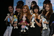 A group of five girls each holding dolls