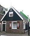 foto van Bakstenen huis met houten bovenbouw op het achtergedeelte