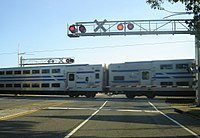Bi-level coaches at grade crossing in Bethpage.