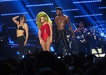 In the center of the photograph is a woman with blonde hair in red clothing; to her sides are two scantily-clad people, and in the background is someone sitting at a drum set.