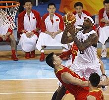 Un joueur américain inscrivant un panier face à un joueur chinois.