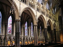 View of the north side of the nave at Lincoln showing wide arcade arches supported on tall slim columns surrounded by shafts of dark marble. The aisle windows are full of stained glass. Beneath them runs a wall arcade in which are displayed a modern set of Stations of the Cross carved in different recycled timbers.