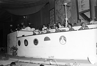 Asian Relations Conference - Two Tibetan delegates (front right) during the Asian Relations Conference in Delhi in 1947 as Mahatma Gandhi speaks (far left). A Tibetan flag is seen in front of them along with flags of other participating countries.