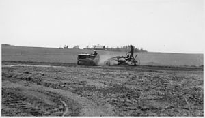 Des Lacs National Wildlife Refuge - Mechanized road-grading. Des Lacs NWR, ND, 1938. A small bulldozer pulls a riding plow in open fields, with farm buildings and crops in background