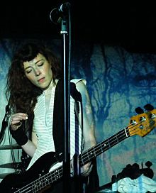 A female musician performing with a bass guitar against a black and blue backdrop. A microphone is visible above her.