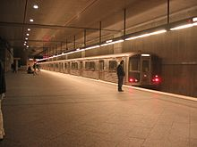 A train is waiting on a track in a subway station. Passengers are standing on the platform.