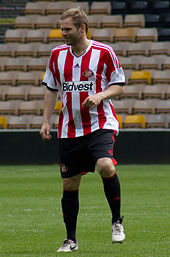 A man with light hair is wearing a red and white striped top, black shorts and black socks. He is standing on a grass field.