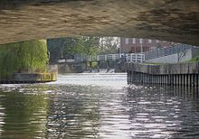 Photograph taken from centre of river underneath a wide-arched bridge. View upstream towards a weir in the far distance.