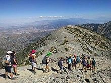 A line of students, many wearing costumes or swimwear, descends toward an alpine ridge