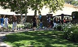 Eine Gruppe von Menschen, die außerhalb eines geschlossenen Bereichs stehen.  Es gibt Bäume, Büsche und Grasflächen.  Ein Großteil des Gebiets, in dem sich die Menschen befinden, wird von den Bäumen am Tor beschattet.