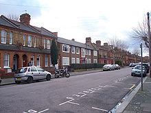 Three houses of an obviously 1950s rectilinear design are surrounded by typical Victorian Gothic houses