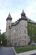Relatively tall and narrow five storied building of grey stone with a dark roof and an attached clock tower.