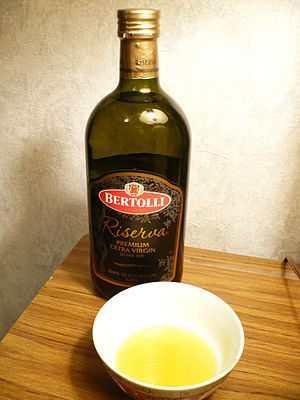 Bertolli - A bottle and bowl of Bertolli Riserva extra virgin olive oil