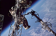 A man dressed in a spacesuit clings to a truss structure, manipulating a second truss with his left hand. Cabling can be seen running along both trusses, and the Earth's horizon can be seen in the background against the blackness of space.
