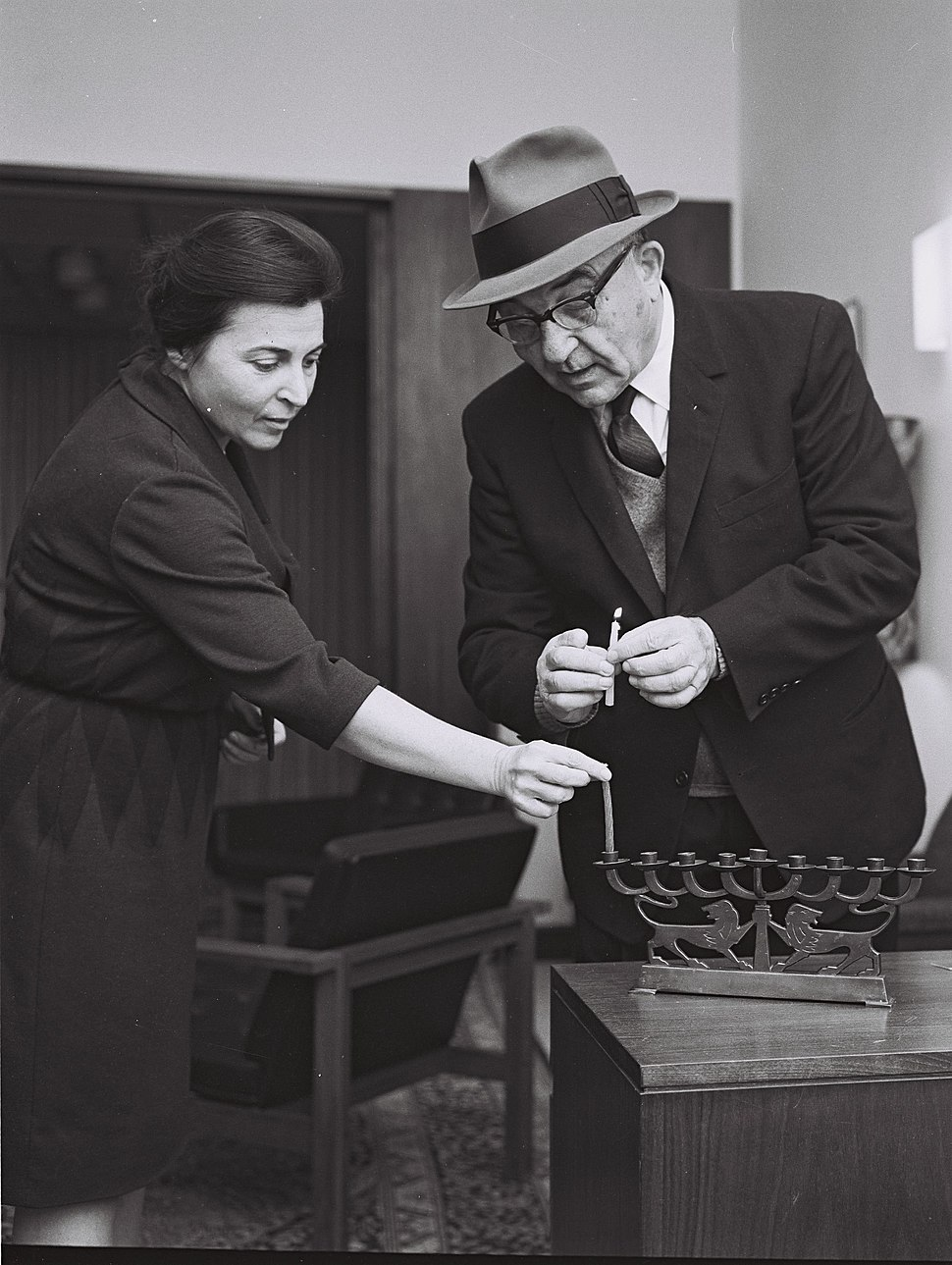 P.M. Levy Eshkol assisted by Mrs. Miriam Eshkol lighting the first Hanuka candle