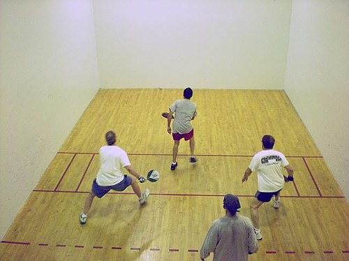 Four men playing paddleball