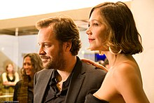 A man and a woman pose together for a photo. The man has short, light-brown hair and a beard, and is wearing a grey suit jacket and grey shirt, the woman has short, shoulder-length brown hair, worn loose, and is wearing large hoop earrings with a sleeveless, strapless black dress.