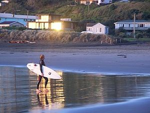 Piha - A surfer leaving the water