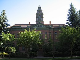 A two-story brick building with a tall tower is partially obscured by trees.
