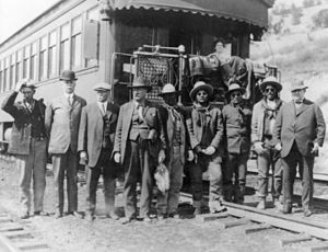 Bluff War - Prisoners of the Bluff War in Thompson, Utah, waiting to board a train for their trial in Salt Lake City. Photo includes Marshal Nebeker, carrying the binoculars, and General Scott, third from left. Chief Polk is standing in between Nebeker and Jess Posey, while Chief Posey stands to the right of Jess, next to Tse-ne-gat.