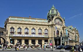 Un grand édifice art nouveau, de couleur claire, au toit de cuivre et au corps central surmonté d'une grande fresque et d'un dôme.