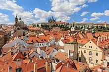 Vue sur une multitude de toits de tuile sous un franc soleil, avec quelques églises, et la cathédrale au loin sur une hauteur.
