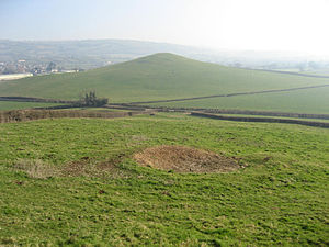 Q-pit - View looking eastwards from Lodge Hill towards Windmill Hill with the Q-pit in the foreground and the Mendip Hills in the background.