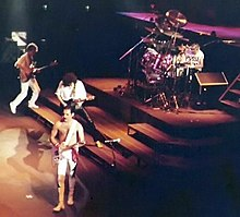 Colour photograph of all four members of Queen performing live in 1981.