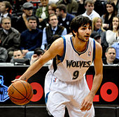 Ricky Rubio in a white Timberwolves uniform dribbling the basketball