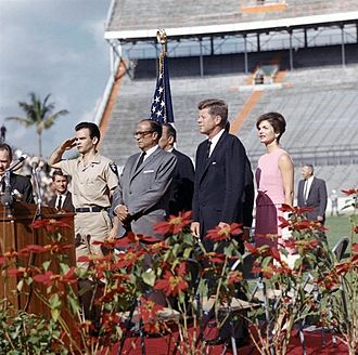 Robert King High - Robert King High stands to the far left of the picture as President John Kennedy addresses the 2506 Cuban Invasion Brigade on December 29, 1962 at the Miami Orange Bowl.