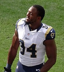 An American football player smiling without a helmet on.
