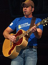A young man in a baseball cap, a blue t-shirt and jeans playing a guitar and singing into a microphone
