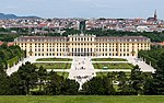 Rococo three- and four-story palace stretches across most of the midground. In the foreground are manacured lawns and walkways, while the background is the old city of Vienna with a cathedral on the horizon.