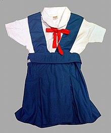 Una camicetta bianca a maniche corte con un ficco rosso a cui è abbinata una gonna-salopette blu Francia
