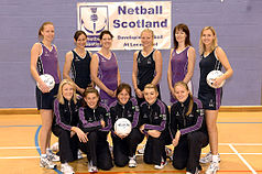 Wearing purple, the netball team is standing in two rows
