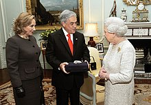 Color image of Chilean President Piñera and the First Lady present a souvenir gift rock from the San Jose Mine to Elizabeth II on 18 October 2010 during a state visit to the UK