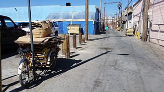 El Segundo Barrio - Cardboard for recycling is piled on a bicycle in front of an alley in Segundo Barrio, 2016.