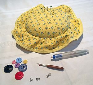 Notions (sewing) - Examples of sewing notions, including a pin cushion, pins, buttons, hooks and eyes, a seam ripper, and sewing chalk