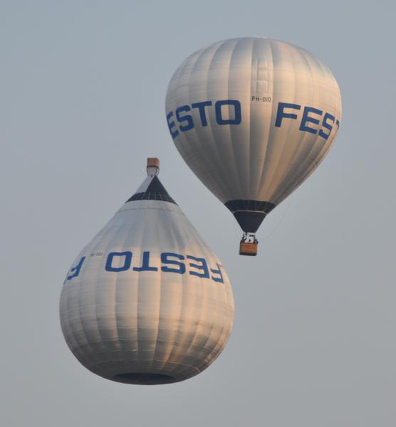 Een luchtballon die ondersteboven vaart (met een namaakmand bovenaan, terwijl de echte mand nauwelijks zichtbaar is).