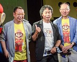 Una imagen de los tres integrantes del staff que trabajaron en el juego.  De izquierda a derecha está el director Takashi Tezuka, el productor Shigeru Miyamoto y el compositor Koji Kondo.