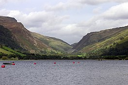 Un lago, con un profundo barranco entre dos montañas más allá