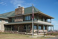 Wooden two-story lodge with green roof, large field stone fireplace, double-decker porch facing a mountain vista.