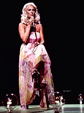 A woman with long blonde hair, wearing a long multi-coloured dress, sitting on a stool and singing into a microphone