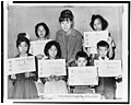 Teacher Miss April Lou with children, recent arrivals from Hong Kong and Formosa, who are holding up placards giving his or her Chinese name and the name to be entered upon the official school records LCCN94512334.jpg