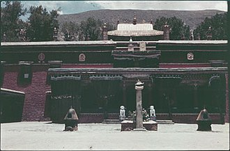 Nechung - The main temple of Nechung monastery, with pillar or doring (rdo ring), 2 incense burners and 2 stone lions behind, before 1950